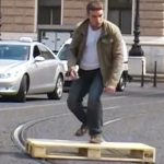 Il fait du skate sur les rails d'un tramway