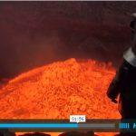 Il s'approche au bord d'un volcan en ébullition